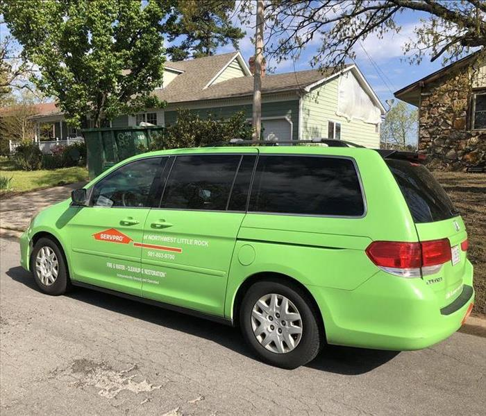 photo of a small green SERVPRO SUV parked at a home