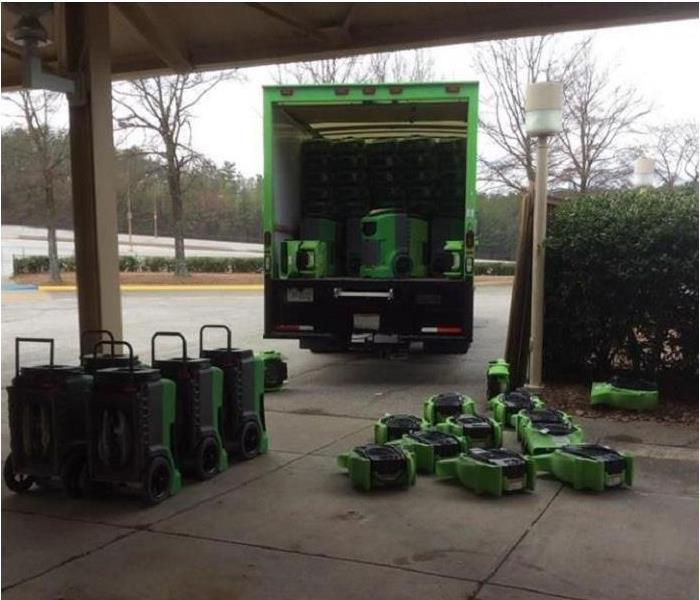 SERVPRO drying equipment stacked on driveway and inside SERVPRO truck