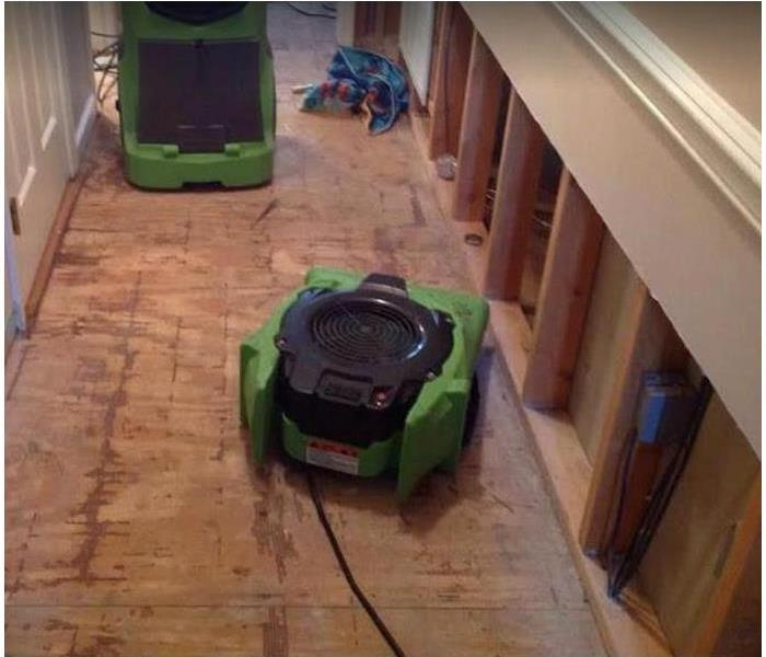 SERVPRO drying equipment being used in water damaged room; flood cuts along walls